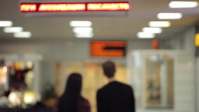 Unfocused back view of couple walking down airport hall. stock video