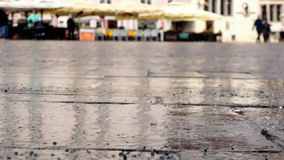 Unfocused blurry walking people on market square while rain is plattering. stock footage