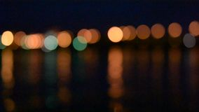 Unfocused city and traffic lights at night near water. With reflections in water stock video footage