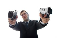 Unfocused criminal businessman with guns. Unfocused criminal businessman with two aimed guns standing over white background Stock Photo