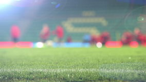 Unfocused footage of footballers (soccer-players) warming up before the match. 
