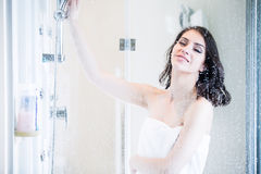 Unfocused portrait of a woman showering through the bath screen with little drops.Relief and relaxation after long stressful day. Royalty Free Stock Photos