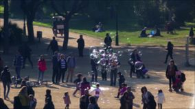 Unfocused scene with people walking in a park of Barcelona.Time Lapse. Unfocused scene with people walking on a holiday in a park of Barcelona, of children stock footage