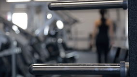Unfocused shooting woman going out in fitness studio. Unfocused shooting woman going on fitness studio. On foreground trainings in gym. Fit active female with stock video