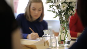 Unfocused view of woman drawing picture with pencil. Making sketch or black and white composition young and pretty female is looking on vase with flowers stock footage