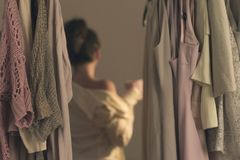 Unfocused young woman with cup of coffee and standing in front of her wardrobe early morning royalty free stock photography