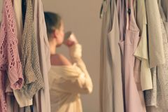 Unfocused young woman with cup of coffee and standing in front of her wardrobe early morning stock photos