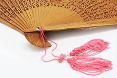 Unfolded Chinese Fan. Extreme close-up of unfolded traditional chinese fan with pink fringe on a white background Royalty Free Stock Photography