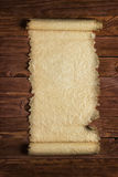 Unfolded paper scroll on a wooden surface, blank background Stock Photos