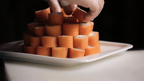 Unfolding sushi rolls philadelphia pyramid on a. Plate. masters work hand in glove. Master in transparent white gloves does the job quickly and competently stock footage