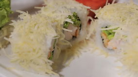Unfolding sushi rolls on a plate. cheese, shrimp and rice, hand craftsmen work gloves. Master in transparent white gloves does the job quickly and competently stock video footage