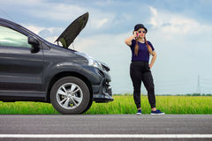 Unfortunate Asian female driver making a phone call Royalty Free Stock Images