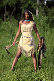 Unfriendly Indian. Aggressive Indian girl with an axe and shield in hand standing in the field Royalty Free Stock Photo
