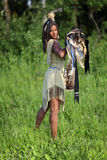 Unfriendly Indian. Aggressive Indian girl with an axe and shield in hand standing in the field Royalty Free Stock Photography