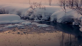 Unfrozen Stream Winter Evening. Seamless Loop. The evening in the winter woods near the unfrozen stream. A lot of snow and a light mist. Seamless loop stock footage