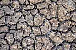 Unfruchtbare Erde Trocknen Sie gebrochene Erde Gebrochenes Schlammmuster Boden in den Sprüngen Creviced Beschaffenheit Dürrenland Lizenzfreie Stockfotografie