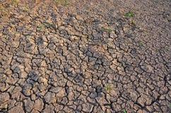 Unfruchtbare Erde Trocknen Sie gebrochene Erde Gebrochenes Schlammmuster Boden in den Sprüngen Creviced Beschaffenheit Dürrenland Stockfotos