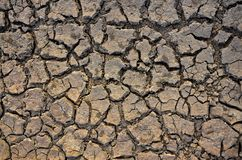 Unfruchtbare Erde Trocknen Sie gebrochene Erde Gebrochenes Schlammmuster Boden in den Sprüngen Creviced Beschaffenheit Dürrenland Lizenzfreies Stockfoto