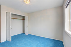 Unfurnished bedroom with blue carpet. Royalty Free Stock Image