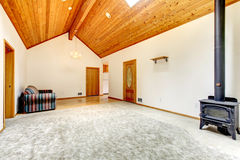 Unfurnished living room with carpet, wood burning stove, and vaulted wood ceiling. Unfurnished living room with carpet, and hard wood Stock Images