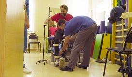 Ungültig im Orthosis bereit, mit Unterstützung gehenden Stocks zwei zu gehen stockfoto