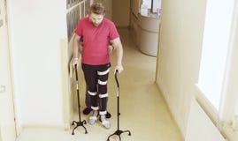 Ungültig im Orthosis, der mit Unterstützung gehenden Stocks zwei geht stockfoto