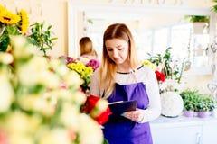 Ung ägare av blomsterhandelhandstil i hennes anteckningsbok Royaltyfri Fotografi