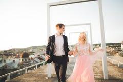 Ung älska kvinna och man som går i händer för stadstakinnehav Royaltyfria Bilder