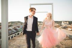Ung älska kvinna och man som går i händer för stadstakinnehav Arkivfoto