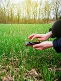 Ung åkerbruk kvinnabiolog som analyserar jord och skörden arkivfoton