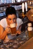 Ung öl för utkast för kvinnligbartenderavsmakning arkivbild