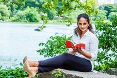 Ung östlig indisk amerikansk kvinna som läser den röda boken som kopplar av på Central Park, New York royaltyfri bild