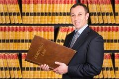 Ung advokat med lagböcker i bakgrunden Arkivfoto