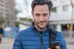 Ung affär som ler mannen i gatan med en mobiltelefon och ett blått omslag royaltyfri bild