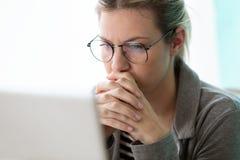 Ung affärskvinna för koncentrat som ser hennes dator, medan tänka i kontoret arkivfoto
