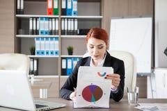 Ung affärskvinna för rödhårig man som kontrollerar pappers med diagram Arkivbild