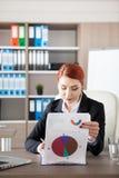 Ung affärskvinna för rödhårig man som kontrollerar pappers med diagram Royaltyfri Fotografi