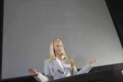 Ung affärskvinna Giving en föreläsning Arkivfoton