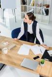 Ung affärskvinna i det moderna kontoret som står över hennes skrivbord royaltyfri bild