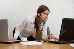 Ung affärskvinna i kontoret med två bärbar dator Royaltyfri Fotografi