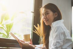 Ung affärskvinna i vitt klänningsammanträde på tabellen i kafé och handstil i anteckningsbok Asiatisk kvinna som använder minnest Arkivbilder