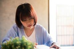 Ung affärskvinna i vitt klänningsammanträde på tabellen i kafé och handstil i anteckningsbok asiatisk kvinna som använder tablete Arkivfoto