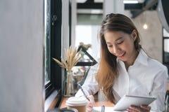 Ung affärskvinna i vitt klänningsammanträde på tabellen i kafé och handstil i anteckningsbok Asiatisk kvinna som använder minnest Arkivbild