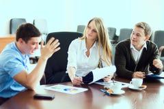 Ung affärskvinna med affärspartners, män på en affär M Royaltyfria Bilder