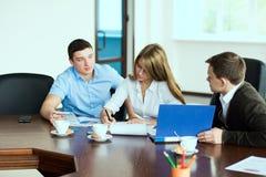 Ung affärskvinna med affärspartners, män på en affär M Royaltyfri Foto