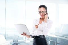 Ung affärskvinna med bärbara datorn och mobilen Arkivfoton