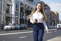 Ung affärskvinna med blå spegelförsedd solglasögon som stannar till telefonen arkivfoton