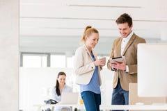 Ung affärskvinna med den manliga kollegan som i regeringsställning använder den digitala minnestavlan Royaltyfria Foton