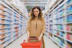 Ung affärskvinna med en livsmedelsbutikshoppingvagn som ser in i en minnestavla i en supermarket mellan hyllor arkivbilder