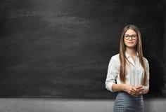 Ung affärskvinna med exponeringsglas som framme står av den tomma svart tavla fotografering för bildbyråer